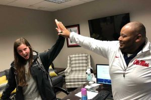 Dr. Sovent Taylor giving student a big high five in congratulations