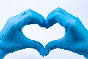 hands in blue gloves making a heart shape