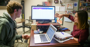 photo of a student and advisor sitting across the desk together with a computer screen between them while the advisor gestures to information on the screen.