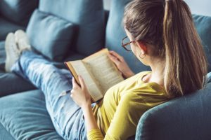 A young woman is sitting on a couch and reading a book