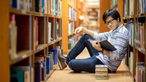 Asian man sitting on the floor between book stacks in a library reading a book